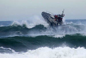 A_motor_lifeboat_braving_heavy_waves_off_Tillamook_Bay,_Oregon